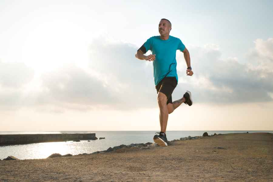 how do i maintain a consistent routine - man running on beach