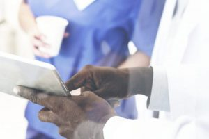 Group of medical professionals having a discussion over a digital tablet
